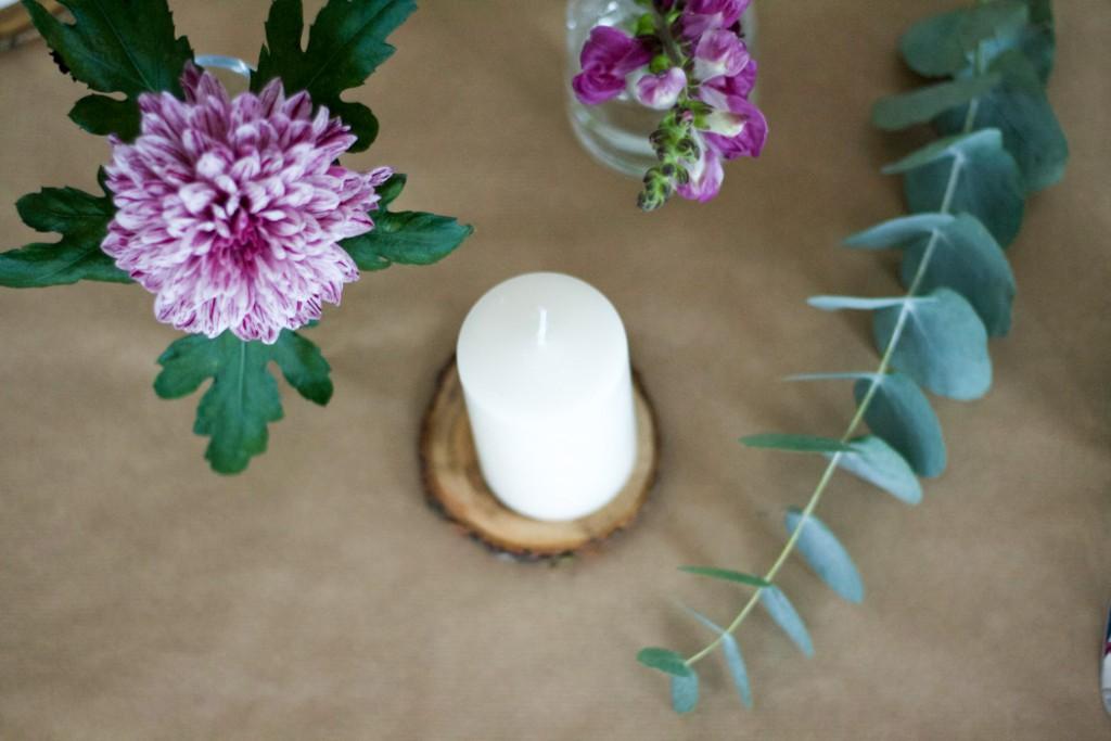 Frühlingstischgedeck mit weißen Kerzen auf Holzscheiben
