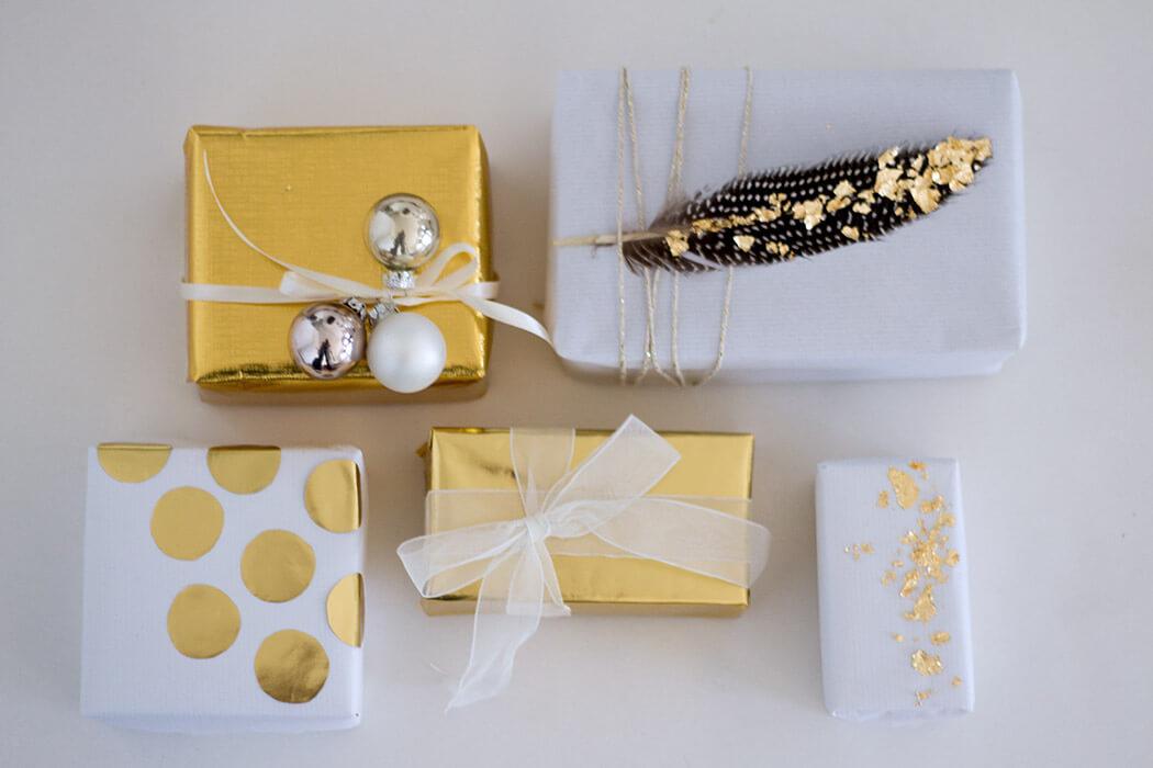 Geschenkverpackung mit gold und weiß Federn, Punkten, schönen Geschenkbändern und Goldflocken DIY Anleitung